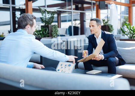 Pleasant smart businessman pointing at the folder - Stock Photo