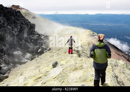 Mountain hiking on Kamchatka Peninsula: two young women tourists walking along sulfur fumarole field in summit crater - Stock Photo