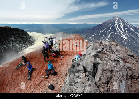 Large group of happy and cheerful tourists and travelers in summit crater of active volcano after hours of climbing - Stock Photo