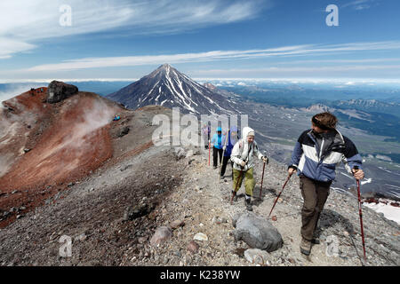 Group of hikers climbing along the edge of summit crater of active Avachinsky Volcano on background of cone of Koryak - Stock Photo