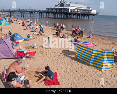 Holidaymakers sunbathing on cleethorpes beach, cleethorpes pier in background. - Stock Photo
