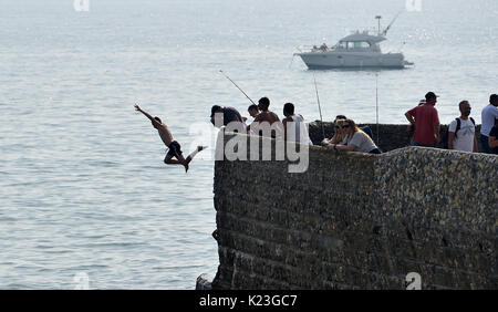 Brighton, UK. 28th Aug, 2017. UK Weather. Youngsters leap into the sea as crowds flock to Brighton beach on Bank - Stock Photo