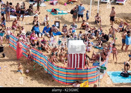 High angle view of beach Punch and Judy show, seen from behind showing crowded enclosed area with children and parents - Stock Photo