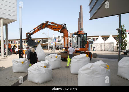 Wolfsburg, Germany. 30th Aug, 2017. An excavator transports sand filled plastic bags, to be used as truck barriers - Stock Photo