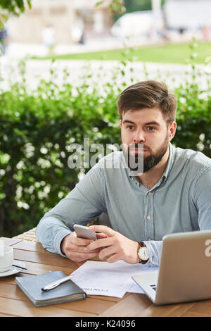 Pensive Businessman  Working in Cafe Outdoors - Stock Photo