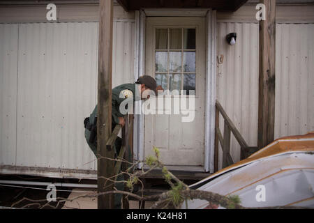 A U.S Border Patrol agent knocks on a door as he searches for survivors among the rubble of a mobile home caused - Stock Photo