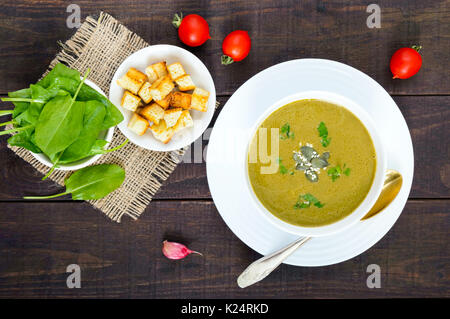 Vegetable cream soup with spinach and potatoes in a white bowl with garlic croutons on a dark wooden background. - Stock Photo