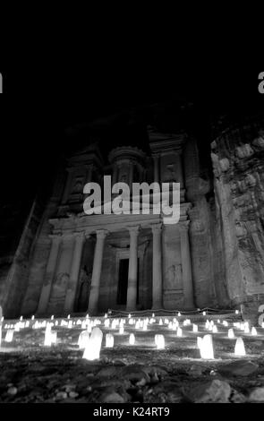 The magic of the Treasury of Petra by night, lit by candles that shed light into the darkness of the desert. - Stock Photo