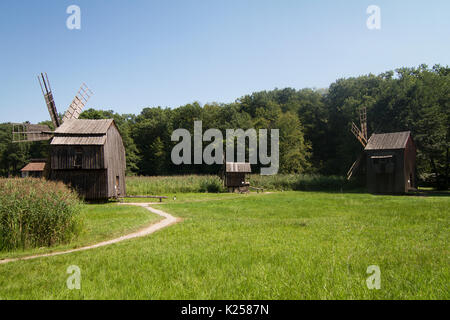 three old wooden windmills on grass near a country road with green forest in the background - Stock Photo