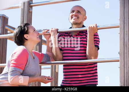 Elderly happy man and woman standing together close to wall bars and smiling - Stock Photo