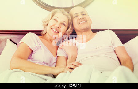 Positive mature adults posing in family bed and smiling - Stock Photo