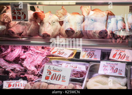 Pigs heads, tongues, trotters, tripe and chicken feet in Kirkgate indoor market in Leeds, Yorkshire, England, UK - Stock Photo