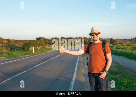 Man with Backpacks and Guitar in casual Travel Clothes walking along road ,Road hitch-hiking. Traveler standing - Stock Photo