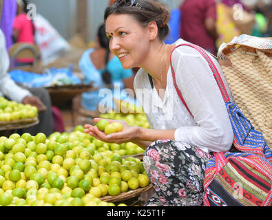 beautiful young woman holding few lemons in hands on market - Stock Photo