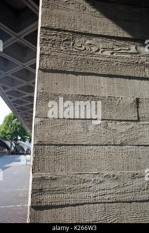 Concrete panels in a brutalist structure show wood grain from being cast in wooden frames - Stock Photo