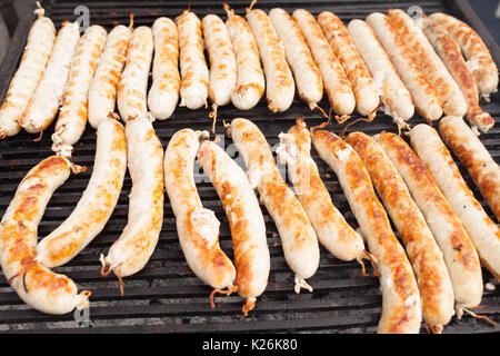 Fresh sausage and hot dogs grilling outdoors on a gas barbecue grill. Street food - Stock Photo