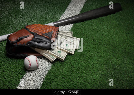 A baseball mitt full of hundred dollar bills on a field with a bat and ball - Stock Photo