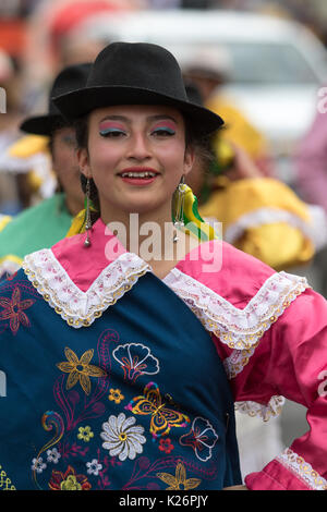 June 17, 2017 Pujili, Ecuador: young indigenous woman in bright color traditional clothing at Corpus Christi parade - Stock Photo