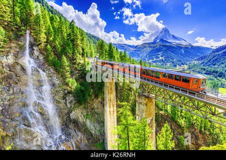 Zermatt, Switzerland. Gornergrat tourist train with waterfall, bridge and Matterhorn. Valais region. - Stock Photo