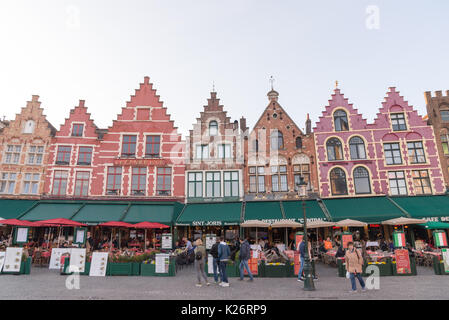 Bruges, Belgium - April 15, 2017: Medieval style shops and restaurants around the market place - Grote Markt in - Stock Photo