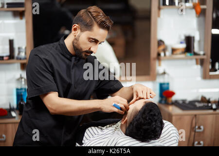 Hairstylist cutting bread of client in modern barber. - Stock Photo