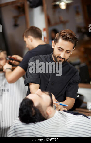 Handsome hairstylist in barber shop cutting bread with razor for brunet man. - Stock Photo
