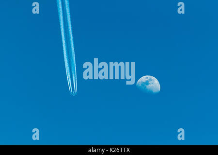 Airplane with condensation trail and moon on blue sky - Stock Photo