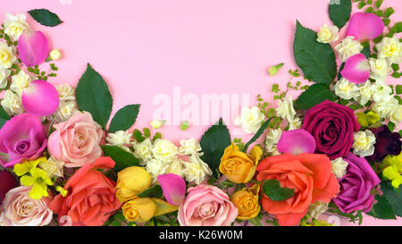Springtime overhead flat lay display of fresh roses and jonquil buds on pink wood table backgound, with copy space. - Stock Photo