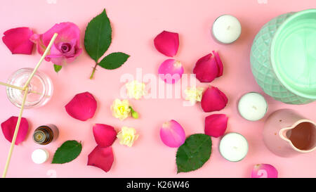 Aromatherapy overhead flatlay display of oil burner, mood sticks, essential oil and scattered rose petals on feminine - Stock Photo