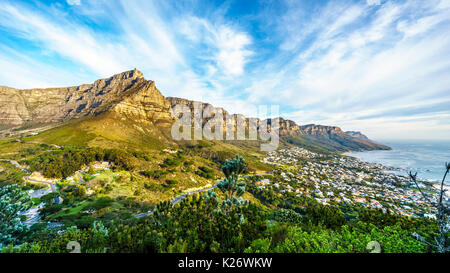 Sun setting over Table Mountain, Camps Bay the Twelve Apostles. Viewed from the hiking trail to the top of Lions - Stock Photo
