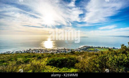 Sun setting over the Atlantic Ocean, Sea Point and Camps Bay. Viewed from Signal Hill at Cape Town, South Africa - Stock Photo