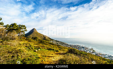 Sun setting over Lions Head and Camps Bay. Viewed from the top of Signal Hill at Cape Town, South Africa - Stock Photo
