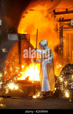 A steel worker in a protective suit taking a 1500 ° hot raw iron sample at the tapping, furnace 8, ThyssenKrupp - Stock Photo