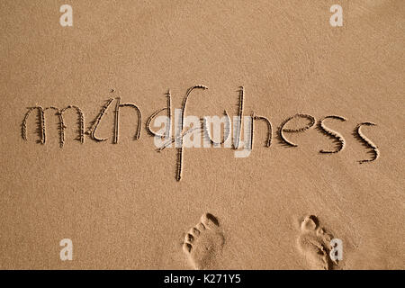 high-angle shot of the word mindfulness written in the sand of a beach and a pair of human footprints - Stock Photo