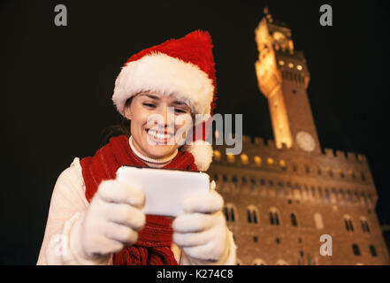 Trip full of inspiration at Christmas time in Florence. Portrait of happy young woman in Christmas hat against Palazzo - Stock Photo