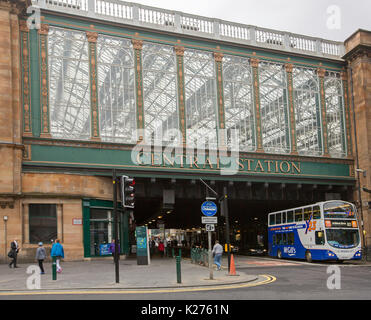 Historic central railway station entrance with double decker bus emerging from tunnel  beneath high glass façade - Stock Photo