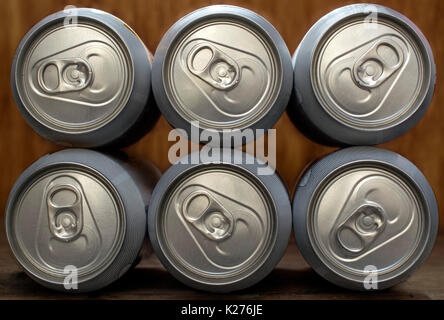 Six frontal organized beer or soda silver aluminum cans, on a wooden background - Stock Photo