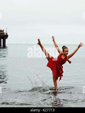 Dancer in red dress splashes in ocean - Stock Photo