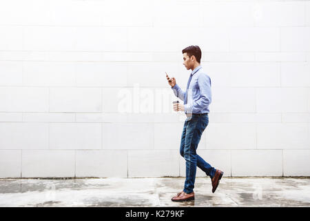 Young motivation Businessman Text or Reading Smart Phone while Walk outdoor building, Lifestyle of modern male, - Stock Photo