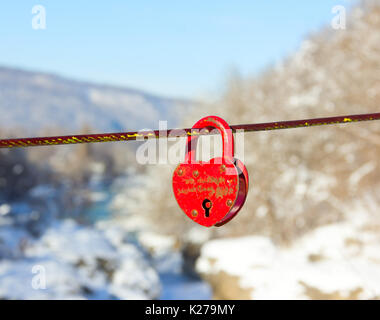 old closed red padlock in heart shape on a background of a winter mountain landscape close up - Stock Photo