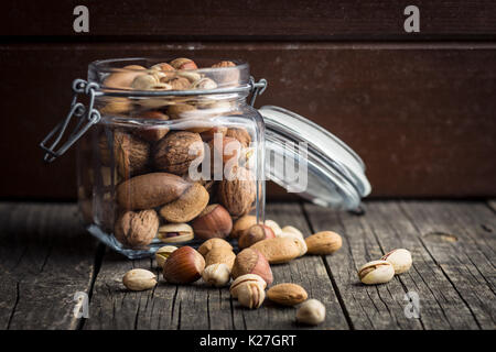 Different types of nuts in the nutshell. Hazelnuts, walnuts, almonds, pecan nuts and pistachio nuts on old wooden - Stock Photo