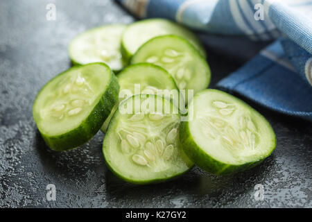 Sliced green cucumbers. Cucumber slices on black table. - Stock Photo