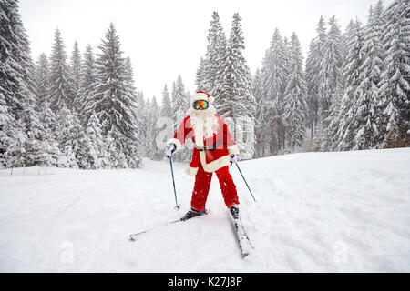Santa Claus skiing in the mountains on snow in winter in Christm - Stock Photo