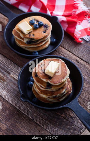 Pancakes with fresh blueberries topped with butter in cast iron skillet served for romantic brunch on rustic table - Stock Photo