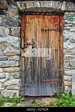 Old wooden door in field stone wall with big rusty hinges and padlock - Stock Photo & Vintage stone wall of an old barn foundation with a hand painted ... Pezcame.Com