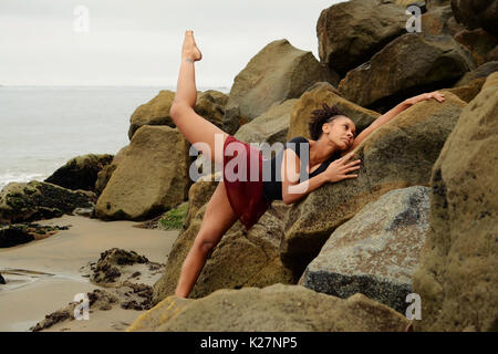 Lyrical dancer stretches on rocks - Stock Photo