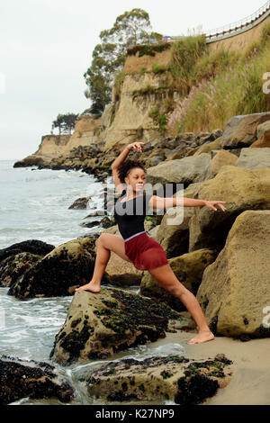 Lyrical dancer poses on rocks - Stock Photo
