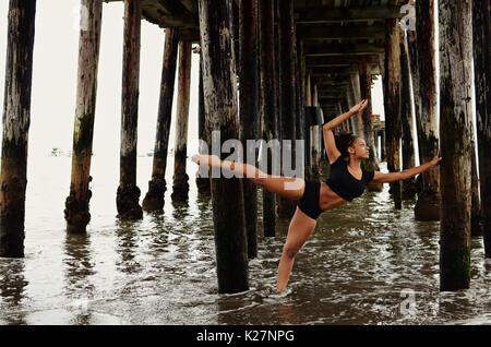 Lyrical dancer under pier - Stock Photo