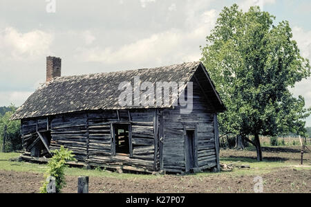 An old abandoned log home with a wood-shingle roof and a brick chimney is slowly falling into disrepair in a farm - Stock Photo