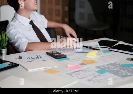 Young Asian Businessman sitting in office and smile in face, selective focus. - Stock Photo